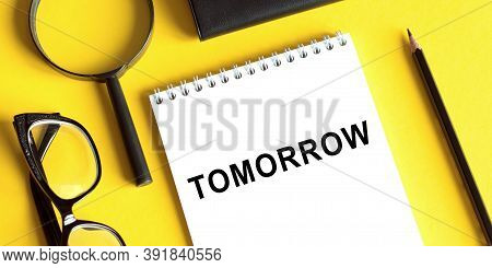 White Notepad With Text 'tomorrow'. Beautiful Yeloow Background. Business Concept.