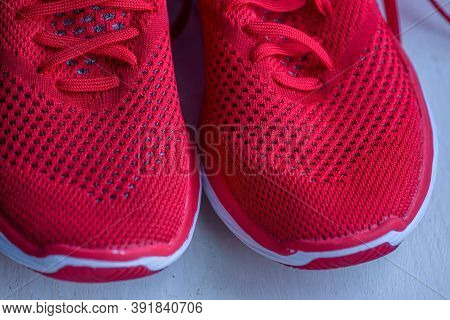 Red Vivid New Sneakers. Red Sneakers. Pair Of Red Sneakers Over Wooden Background Top View Flat Lay.