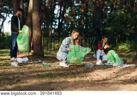 Group Of Female And Male Volunteers Keep Nature Clean And Picking Up Rubbish At The Forest. Nature L