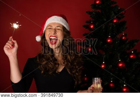 Beautiful Long-hair Brunette Girl In Santa Claus Hat Fun Singing Holiday Songs With Burning Sparkler