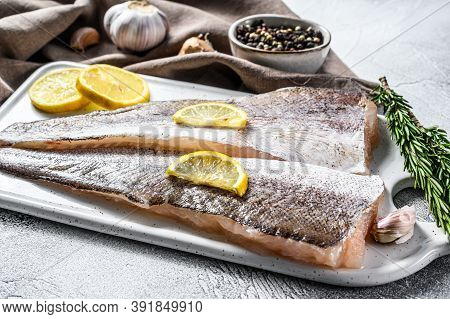 Fresh Raw Hake Fish Fillet With Pepper And Lemon. White Background. Top View