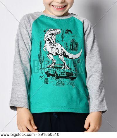 Close-up Of Smiling Giggling Frolic Kid 5-6 Y.o. Boy In Grey Sweatshirt With Dinosaur T-rex Riding O
