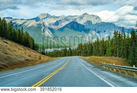 Rural Road In The Forest With Mountains In The Background. Alberta Highway 11 (david Thompson Hwy) A