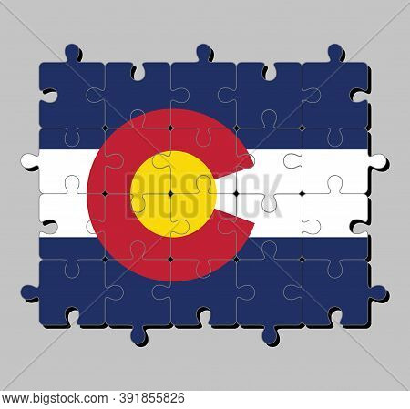 Jigsaw Puzzle Of Colorado Flag In Blue White And Blue. On Top Of These Stripes Sits A Circular Red