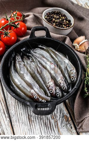 Raw Smelt With Pepper And Thyme In A Pan. White Background. Top View