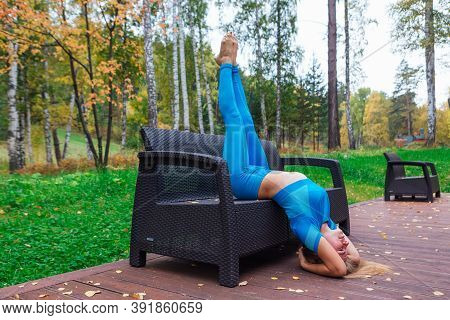 Young Woman Doing Yoga Exercises On The Bench In Autumn Park.