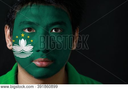 Portrait Of A Man With The Flag Of The Macau Painted On His Face On Black Background, Green With A L