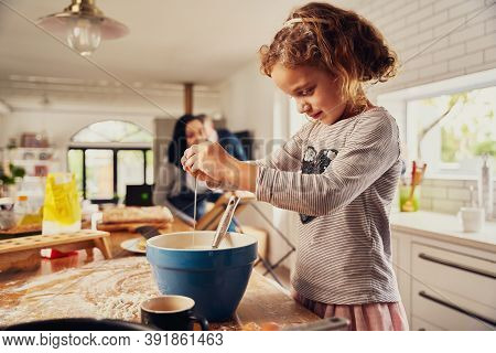 Cute Little Girl Child Breaking Egg In A Bowl While Preparing Dough In Messy Kitchen Counter At Home
