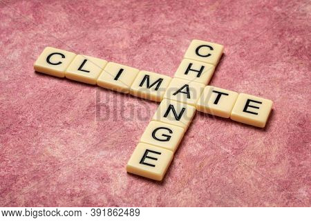 climate change crossword in ivory letter tiles against textured handmade paper,  global warming concept