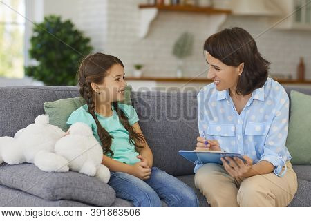 Happy Little Child Communicating With Psychologist Sitting On Sofa During Therapy Session At Home