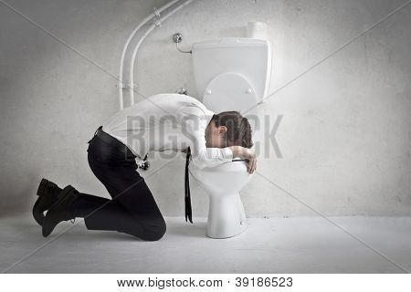 Young man in tie puts his head in a toilet