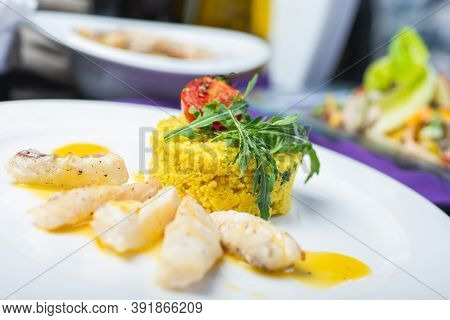 Fillet Of White Fish In Sauce On A Plate With Garnish And Herbs. Full Lunch, Main Courses On A White