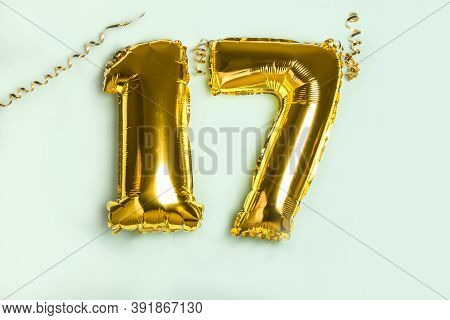 Decoration For Seventeen Birthday Party. Golden Balloon In Form Of 17 Number On Blue Background