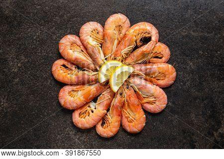 Boiled tiger prawns on black table. Top view. Tasty shrimps.