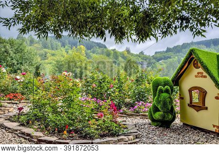 Novokuznetsk, Russia - August 15, 2020: Green Sculpture Of Squirrel Near Little House, Created From