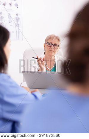 Mature Medical Physician Explaining Treatment To Nurses During Healthcare Seminar. Clinic Therapist