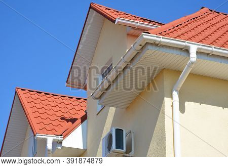 A Stucco House With A Red Metal Roof, Attic And Air Conditioner Outdoor Unit With A Close-up On A Wh