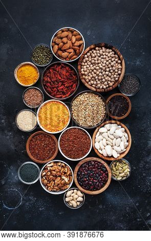 Superfoods, Legumes, Nuts, Seeds And Cereals Selection In Bowls On Grey Background. Superfood As Chi