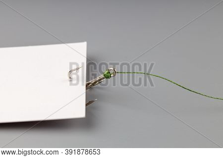 White Business Card On A Gray Background Hooked With A Fishing Hook Tied To A Thread. Tying And Luri