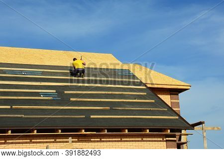 A Building Constructor Is Installing Roofing Underlayment, Waterproof, Moisture Protection On The Ro