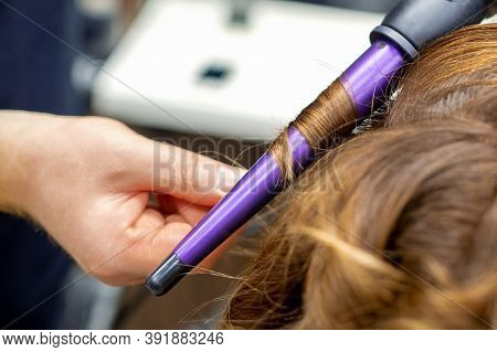 Professional Hairdresser Makes Curly Hairstyle By Curling Iron For Long Red Hair Of Young Woman In H