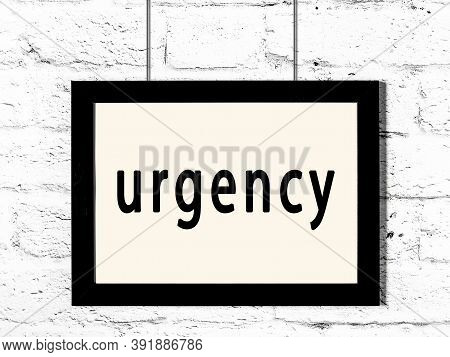 Black Wooden Frame With Inscription Urgency Hanging On White Brick Wall