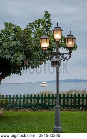 Old Lamppost With Glowing Lanterns On The Embankment In The Evening. Green Lawn, Terrace On The Beac