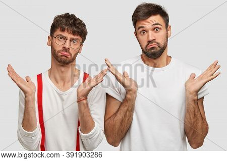 Photo Of Two Carefree Clueless Bearded Men Shrug Hands Spread Aside, Have Hesitant Facial Expression