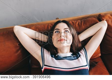 Young Calm Caucasian Woman Relaxing Lying On Comfortable Sofa In Modern Living Room, Lazy Happy Woma