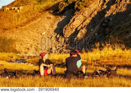 Group Of Trekkers Resting In Sunset Sunbeams In High Mountains. Young Men And Women Hiking Near Sary