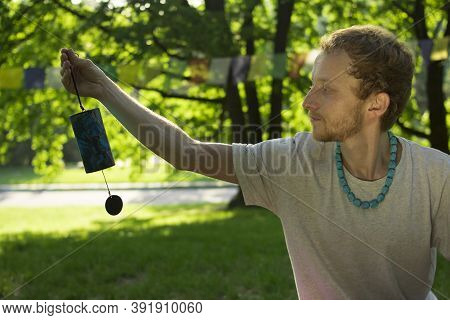 Buddhist Man Holds In His Hands A Buddhist Black And Blue Bell On A Background Of Nature