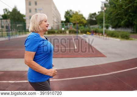 Mature Woman Running In Early Morning. Attractive Looking Mature Woman Keeping Fit And Healthy.
