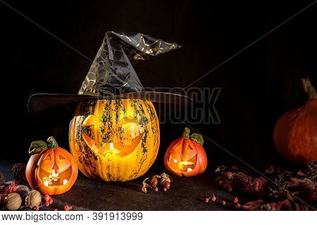 Carved Pumpkins For Halloween, Jack's Head Is On The Table. Pumpkin In A Witch's Hat. Dark Backgroun
