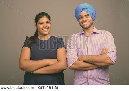 Young Indian Couple Together And In Love Against Gray Background