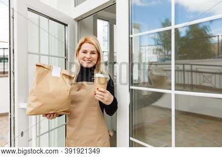 Beautiful Young Woman In Apron And Leaning Against Doorway Of Wall Coffee House Or Restaurant As Own