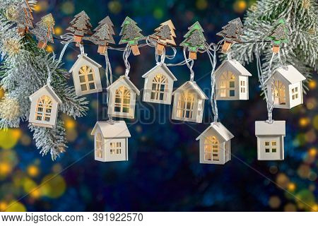 Christmas Background Of A Garland Of Lights In The Form Of Houses On Snowy Fir Branches On Dark Back