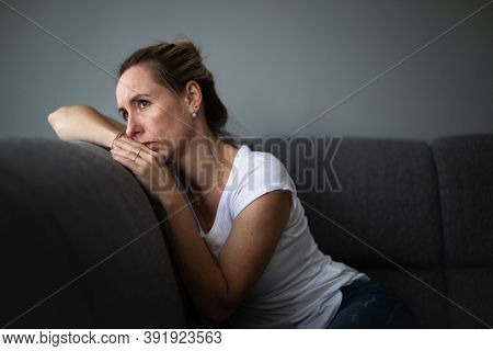 Depressed mid-aged woman at home feeling sad, lonely, anxious (color toned image)