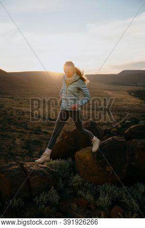 Caucasian Female Joking On Top Of Luscious Mountain Hills At Sunset