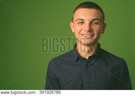 Studio Shot Of Young Handsome Businessman Against Green Background