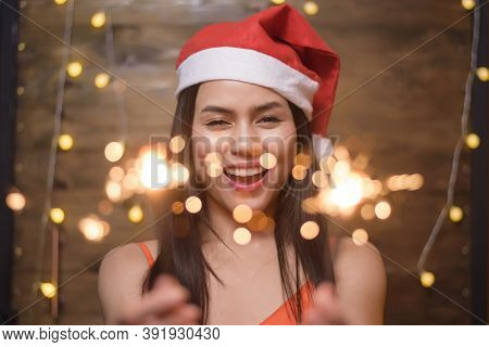 Portrait Of Beautiful Woman Wearing Red Santa Claus Holding Sparklers At Home, Christmas And New Yea