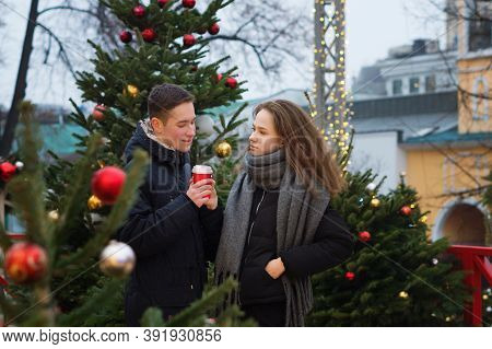 Young Boy And Girl Are Having Fun Outdoor At Christmas Market. Cute Couple Spends Time Together At T