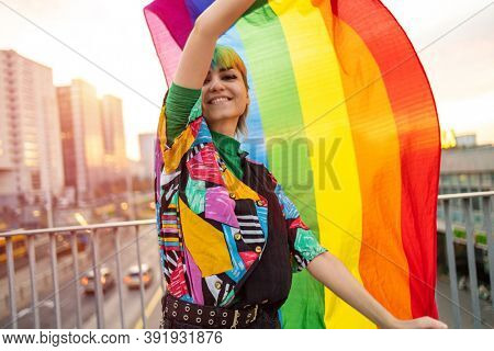 Portrait of happy non-binary person waving rainbow flag