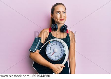 Beautiful young blonde sporty woman holding weight machine to balance weight loss smiling looking to the side and staring away thinking.