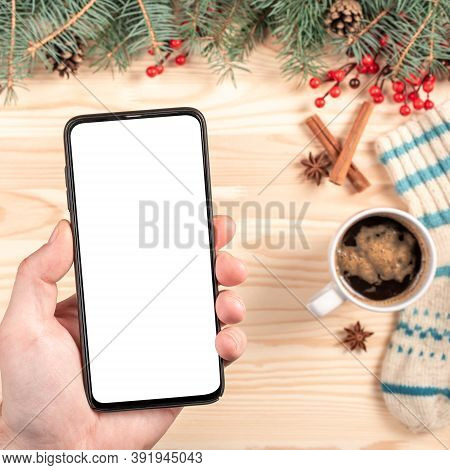 Mockup Phone On Christmas Background. Top View Of A Man Holding A Phone With Blank White Screen In H