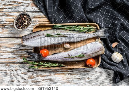 Fresh Pollock Fish. Raw Seafood. White Wooden Background. Top View