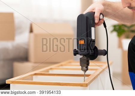 Unrecognizable Furniture Assembler Man Assembling Cabinet Shelf Working Using Electric Drill Indoors