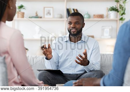 Marital Therapy. Black Man Professional Psychologist Consulting Married Couple On Meeting At His Off