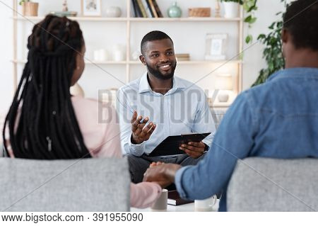 Couples Therapy Session. Counselor Talking To Black Husband And Wife On Meeting At Office, Giving Ad