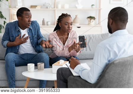 Jealous Wife. Angry Black Woman Showing Husbands Phone To Counselor, Blaming Him For Cheating And In