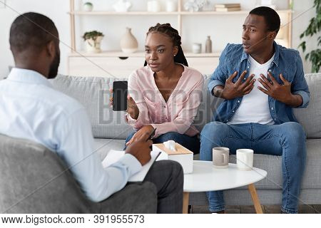 Reconciling After Infidelity. Wife Showing Cheating Husbands Phone To Psychologist During Family The